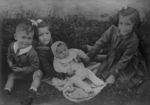 Tre bambini con neonato